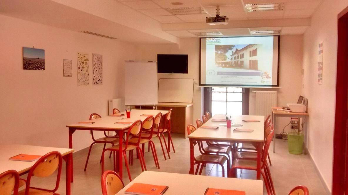 Salon, avec disposition des tables pour une classe découverte, avec rétroprojecteur