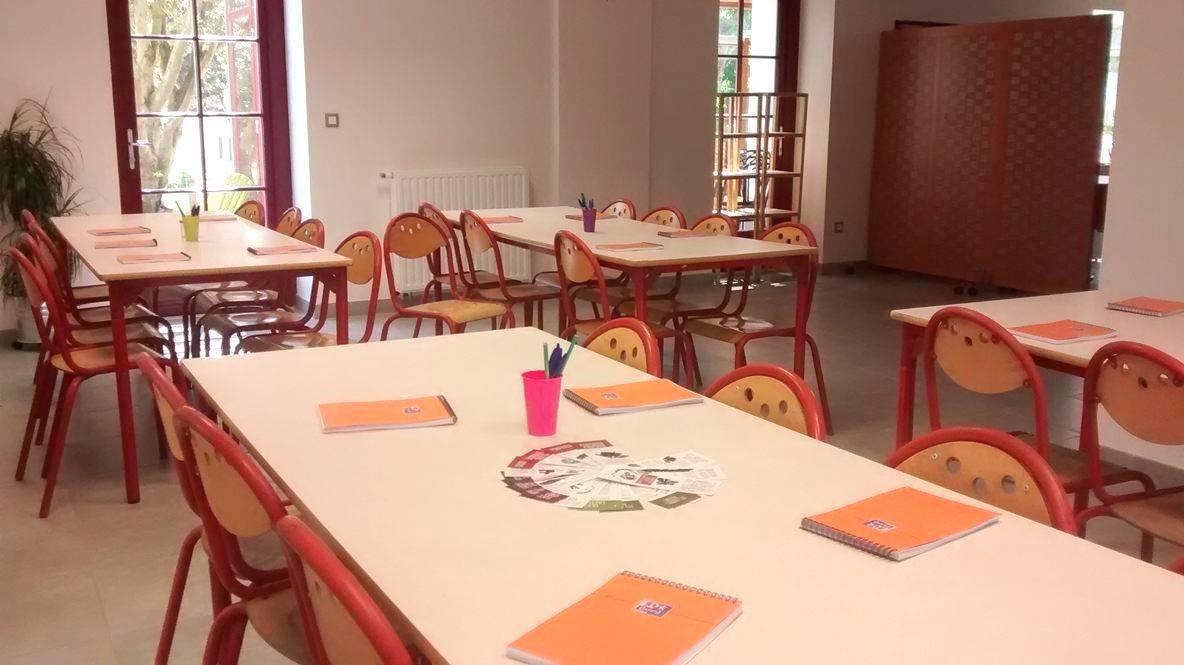 Salon, avec disposition des tables pour une classe découverte